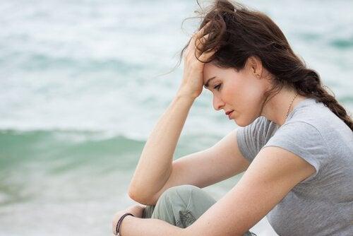 En bekymret kvinde ved havet