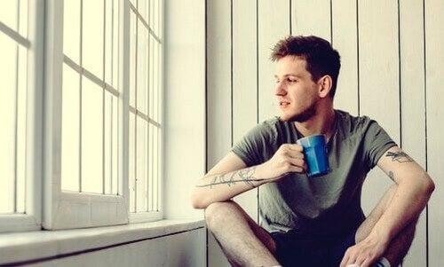 Mand drikker en kop kaffe, mens han kigger ud af vinduet