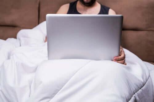 Mand i seng med computer