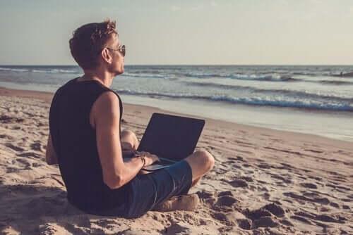 Nedgearing illustreres af mand med computer på strand