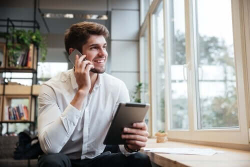 Mand med tablet, der snakker i mobil