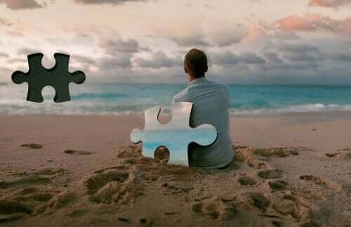 Mand på strand med stor puslespilsbrik fra himlen