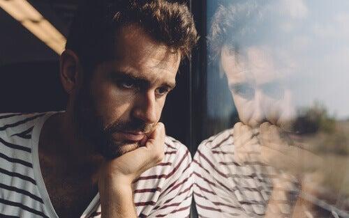 Mand ser ud af vindue og er overvældet af følelsesmæssig overbelastning under lockdown