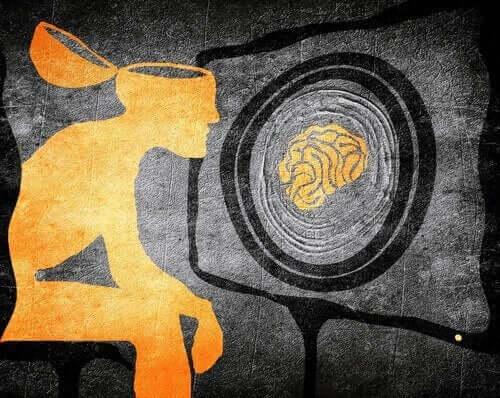 Figur med åben hjerne foran TV