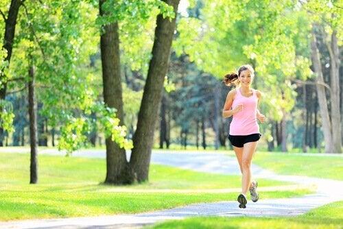 Træning er en god stresshåndteringsmetode, hvilket kvinde anvender ved at løbe i skov