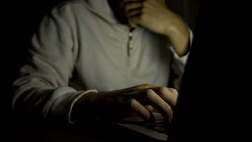 Mand ved computer i mørke