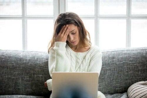Stresset kvinde ved computer oplever frygt for at miste jobbet