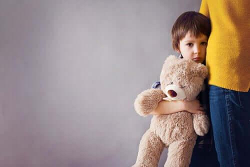 Barn med bamse i armene står tæt på voksen