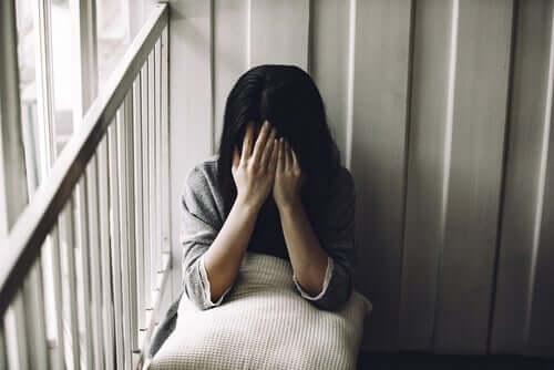 Trist kvinde, der holder sig for ansigtet