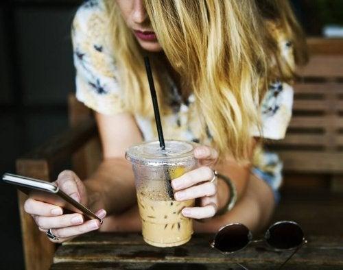 Ung kvinde, der får en iskaffe og bruger sin mobil