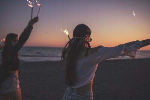 Unge på stranden med stjernekastere
