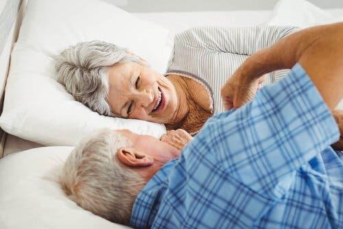 Ældre par, der ligger i seng og griner