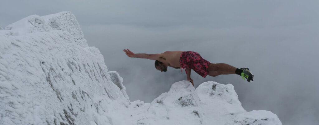 Mand balancerer på toppen af isbjerg