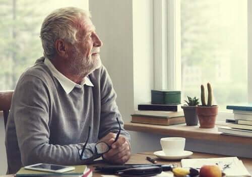 Ældre mand, der ser ud af vindue