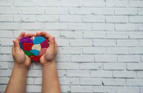 Børnehænder der holder et hjerte af modellervoks