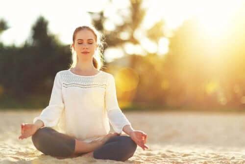 Kvinde mediterer på en strand