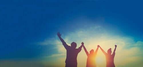 Glade mennesker hæver armene over hovedet