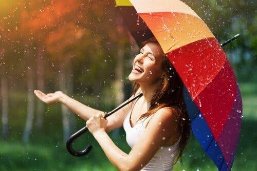 Glad kvinde i regnen under paraply
