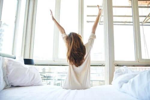 Kvinde strækker sig siddende ved sengen