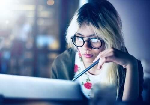 Kvinde ved computer kæmper med at arbejde og studere samtidig
