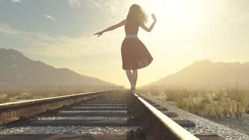 Kvinde, der går på kanten af togskinner