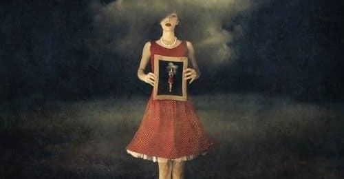 Kvinde, der holder et maleri af sig selv