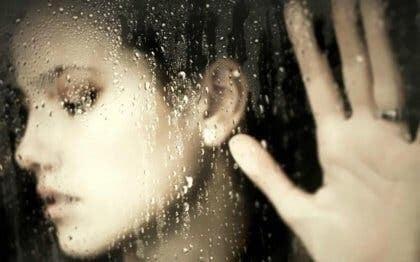 Kvinde bag regnvåd rude
