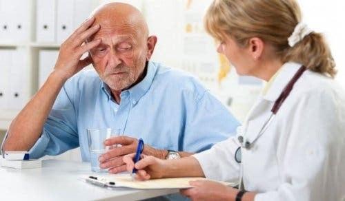 Læge, der forsøger at kommunikere med mand med demens