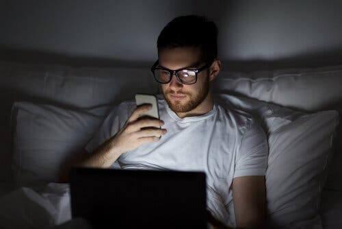 Mand i seng med telefon og computer