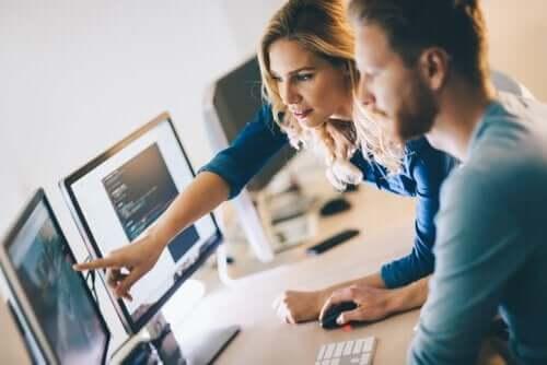 Mand og kvinde ved flere computerskærme