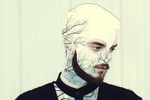 Mand med grene fra træer i ansigtet