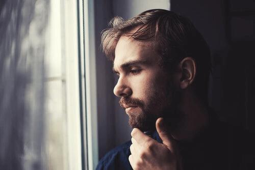 Mand ved vindue tænker over, hvordan han kan hjælpe under lockdown