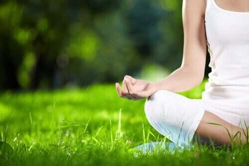 Kvinde mediterer på en plæne