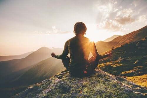 Mand mediterer i bjergene for at kunne træffe beslutninger med mindfulness