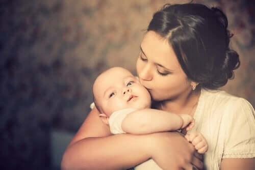 Mor, der kysser baby på kinden