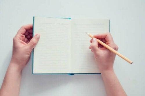 Person med blank notesbog og blyant
