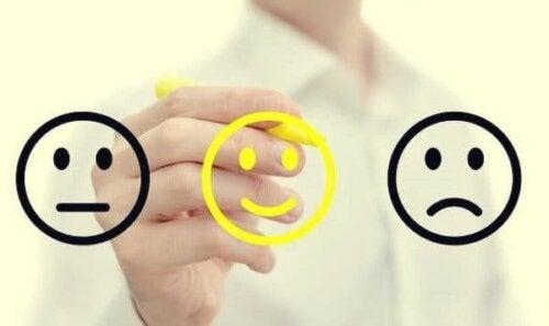 Person, der tegner forskellige smileyer
