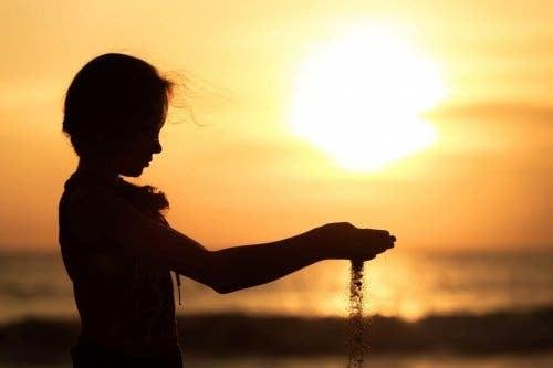 Pige med sand, der risler mellem hænderne