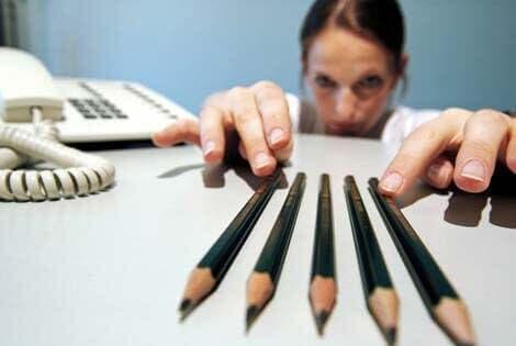 Kvinde studerer fem blyanter