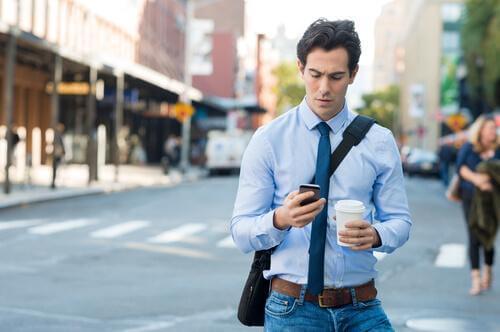 En mand med kaffe og smartphone