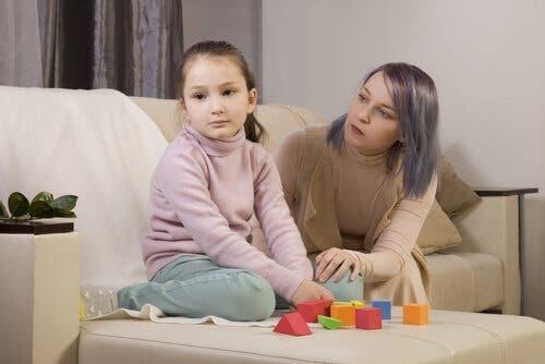 Mor prøver at skabe kontakt til pige på sofa