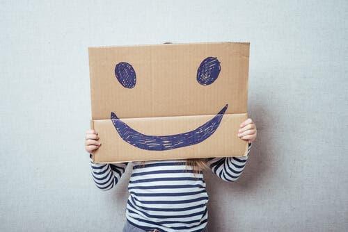 Følelsesmæssig uddannelse: Et barn bag et smiley papskilt