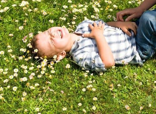 Barn griner i græs
