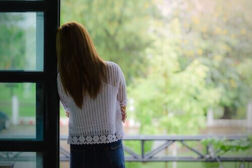 En kvinde, der kigger ud af vinduet
