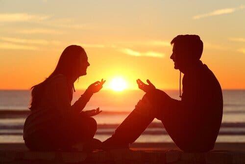 Mand og kvinde taler sammen på strand foran solnedgang