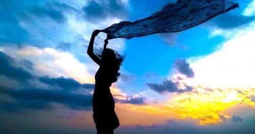 Kvinde, der holder et sjal i vind
