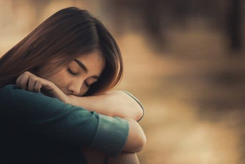 Kvinde, der omfavner sig selv med lukkede øjne