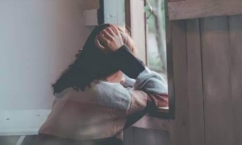 Kvinde, der sidder trist ved vindue