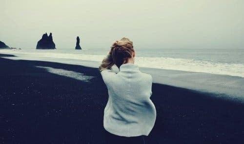 Kvinde, der sidder ved strand, tænker over, hvordan man reagerer på forskellige situationer