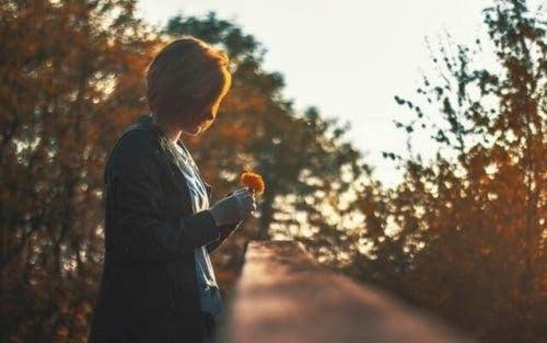 Kvinde, der står udenfor med en blomst i hånden